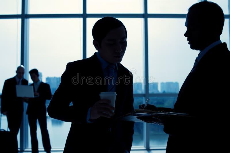 Hombres de negocios en terminal de aeropuerto foto de archivo