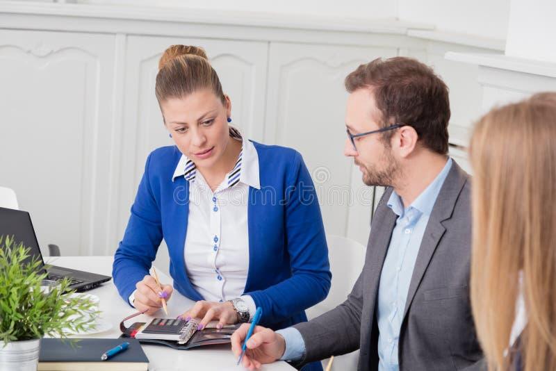 Hombres de negocios en una reunión que se sienta en el escritorio de la conferencia foto de archivo libre de regalías
