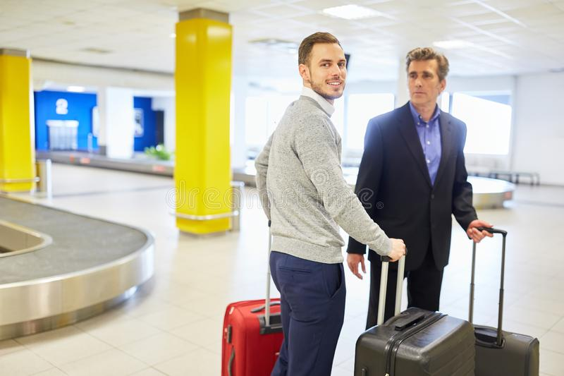 Hombres de negocios en viaje de negocios en la demanda de equipaje imagen de archivo libre de regalías