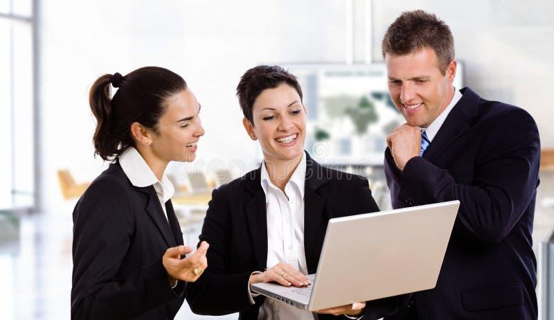 Hombres de negocios felices con el ordenador portátil imagen de archivo