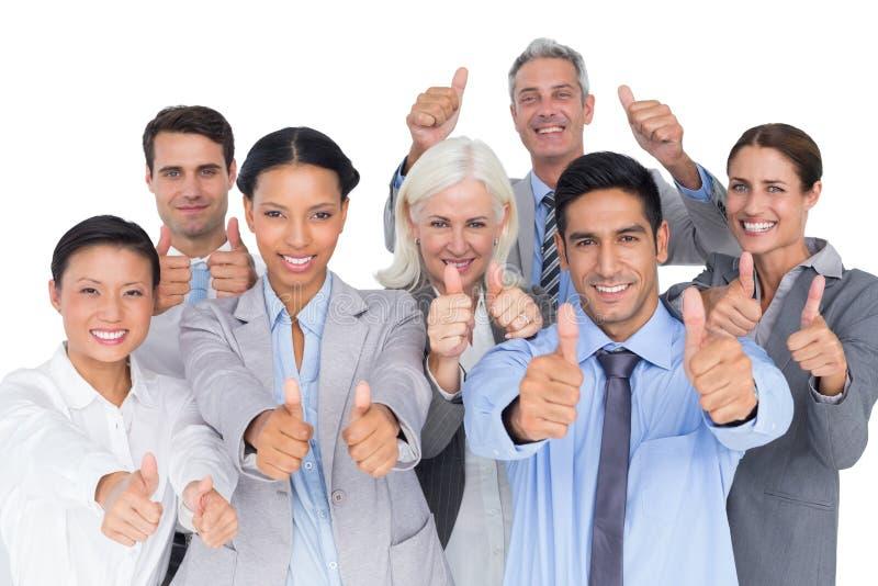 Hombres de negocios felices con los pulgares para arriba que miran la cámara fotos de archivo libres de regalías