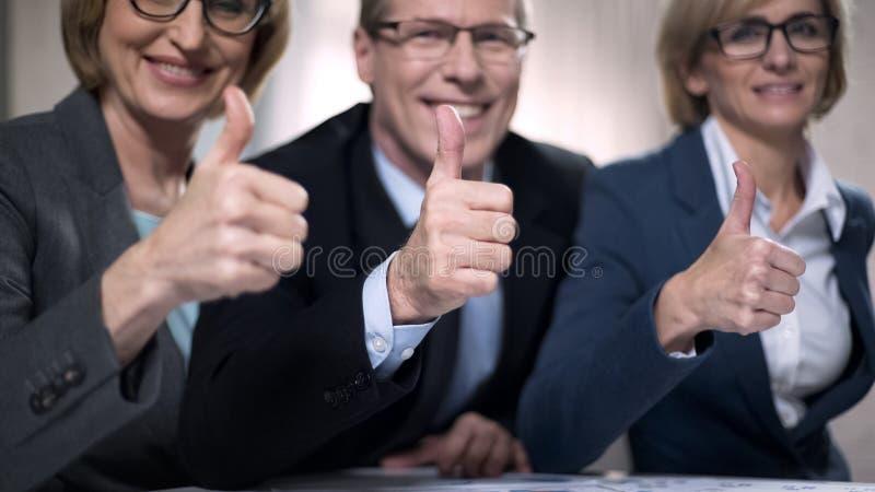 Hombres de negocios felices con los pulgares para arriba, satisfecho con la presentación acertada fotografía de archivo libre de regalías