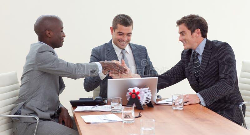 Hombres de negocios felices en una reunión que mira una computadora portátil foto de archivo libre de regalías