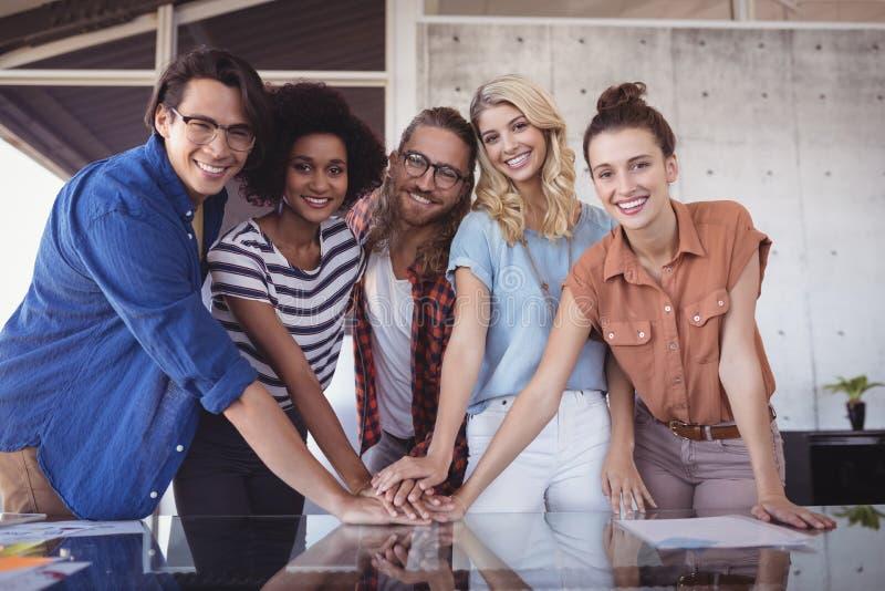 Hombres de negocios felices que apilan las manos en la tabla en oficina creativa foto de archivo libre de regalías