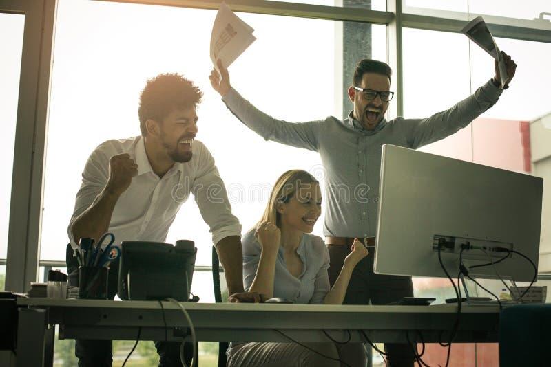 Hombres de negocios felices que gozan en trabajo acertado imagen de archivo libre de regalías