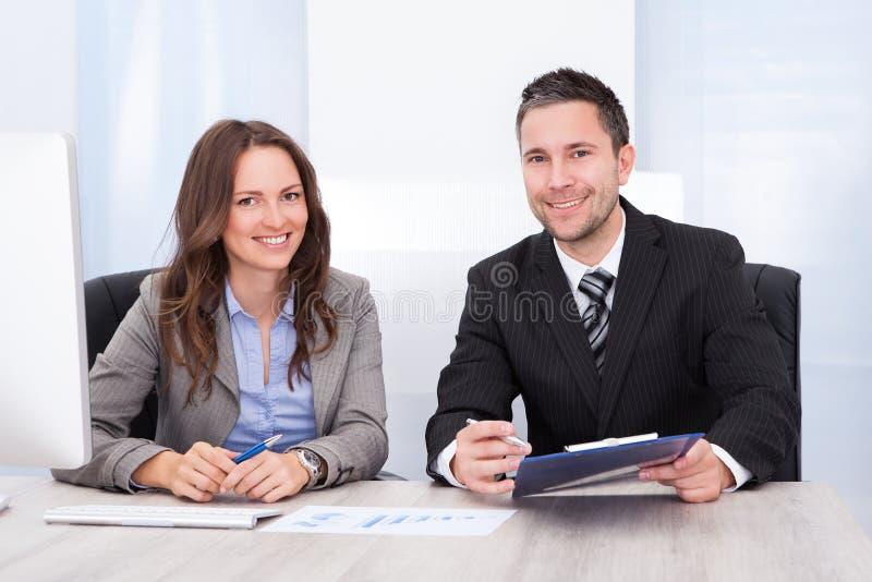 Hombres de negocios felices que se sientan en el escritorio que sostiene el tablero fotos de archivo libres de regalías