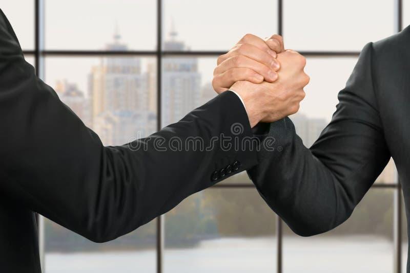 Hombres de negocios fuertes y apretón de manos amistoso imagenes de archivo