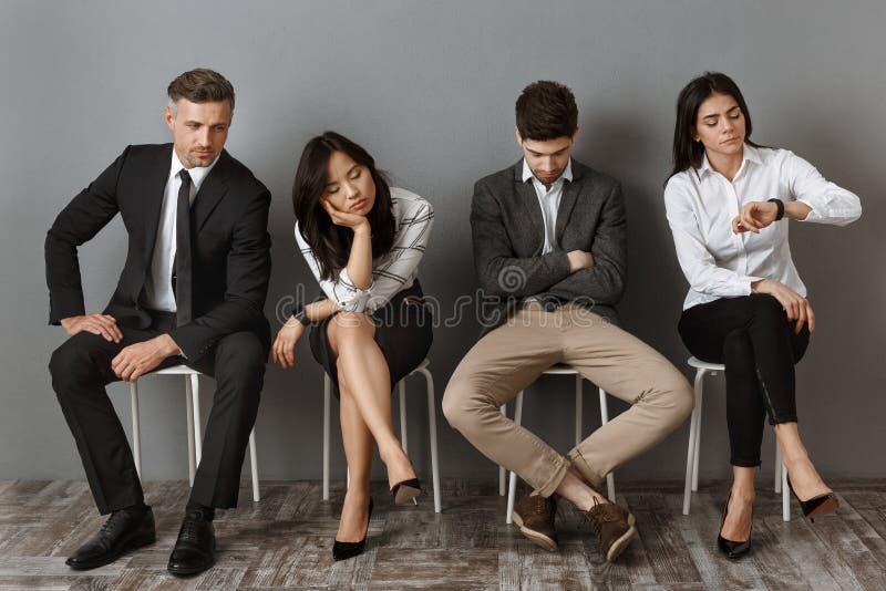 hombres de negocios interraciales aburridos y cansados en esperar del desgaste formal imágenes de archivo libres de regalías