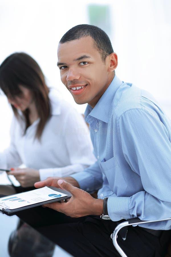 Hombres de negocios jovenes acertados con el documento financiero imágenes de archivo libres de regalías