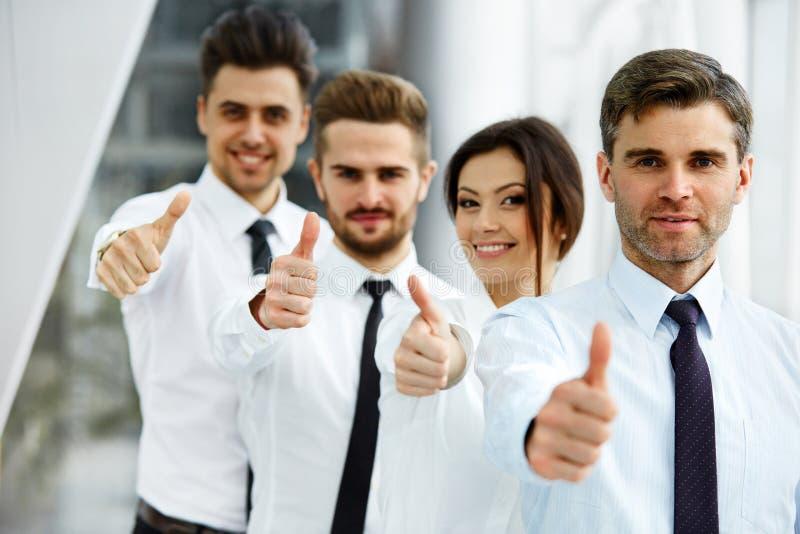 Hombres de negocios jovenes acertados que muestran los pulgares para arriba fotos de archivo libres de regalías