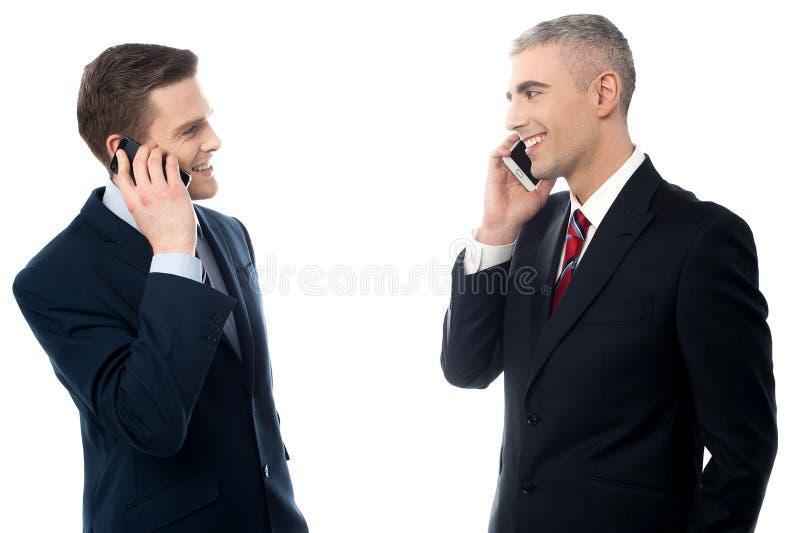 Hombres de negocios jovenes con los teléfonos celulares imágenes de archivo libres de regalías