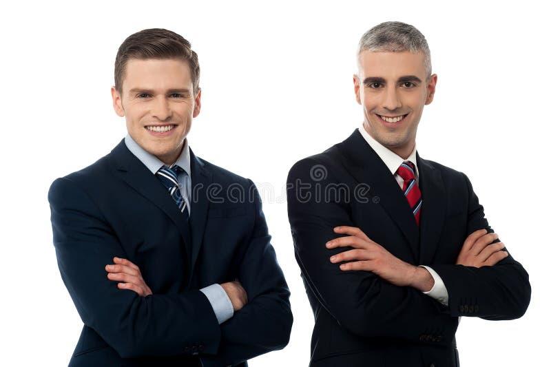 Hombres de negocios jovenes confiados aislados en blanco fotos de archivo