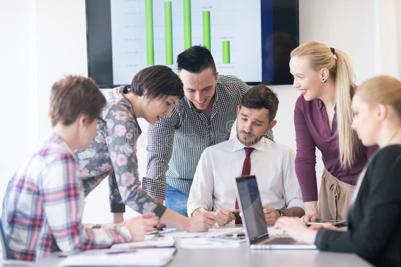 Hombres de negocios jovenes del grupo en la reunión en la oficina moderna foto de archivo