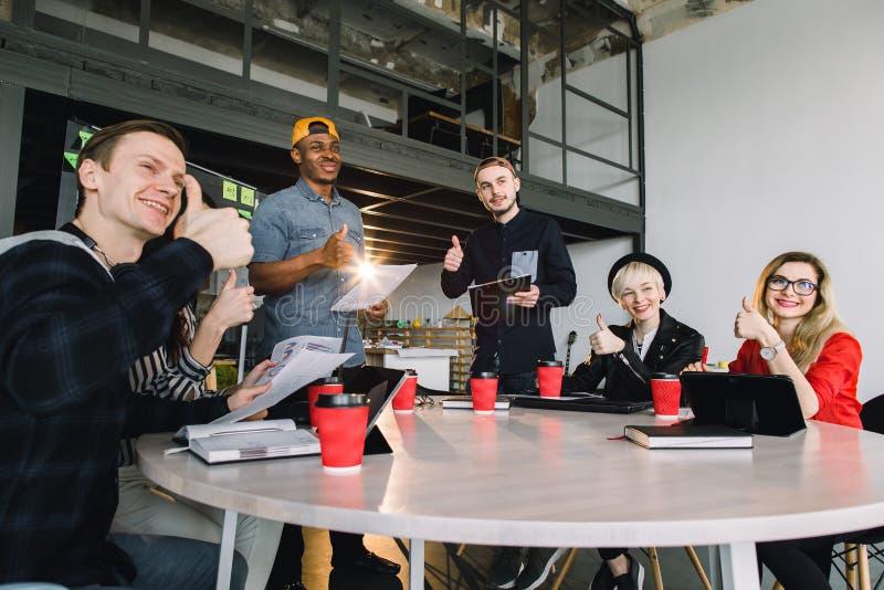 Hombres de negocios jovenes del grupo recolectados junto discutiendo idea creativa Grupo de estudiantes internacionales que se si imagen de archivo libre de regalías