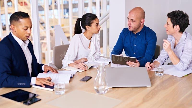 Hombres de negocios jovenes el hablar ocupado el uno al otro en la reunión foto de archivo