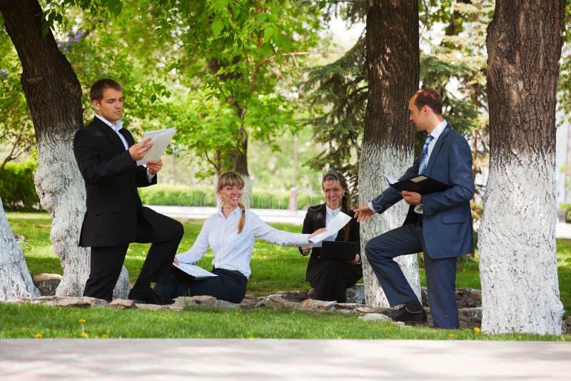Hombres de negocios jovenes en un parque imagen de archivo