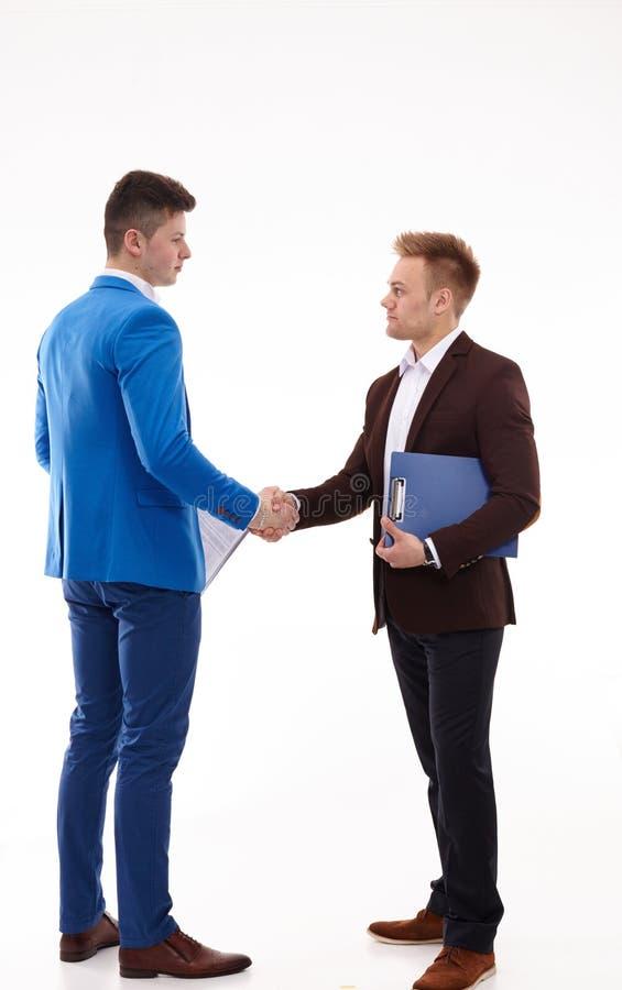 Hombres de negocios jovenes hermosos que sacuden las manos, colocándose foto de archivo libre de regalías
