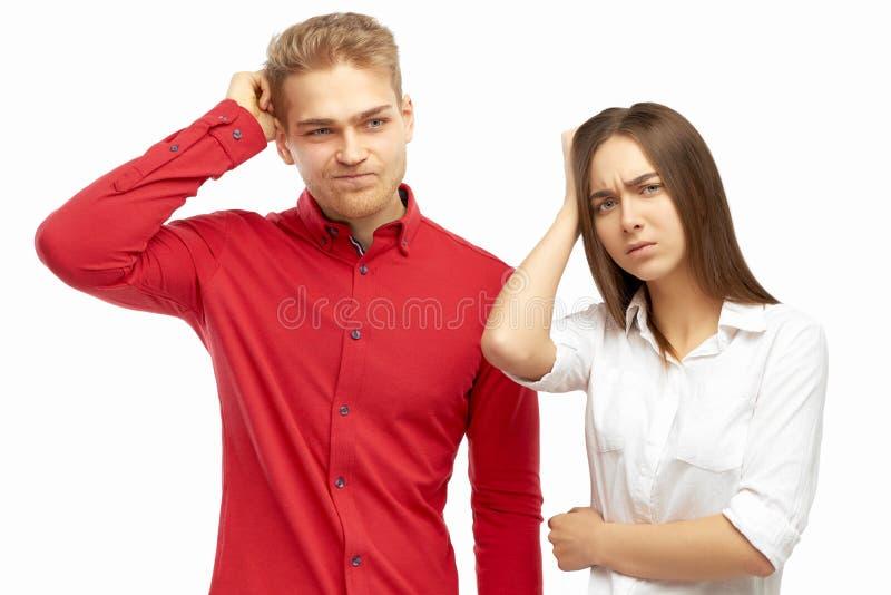 Hombres de negocios jovenes de moda atractivos que miran lejos con la expresión decepcionada confusa, rasguñando la cabeza fotos de archivo