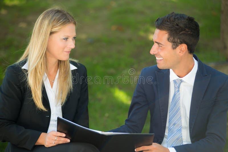 Hombres de negocios jovenes que discuten al aire libre foto de archivo
