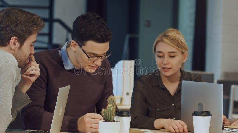 Hombres de negocios jovenes que discuten en sala de reunión en la oficina creativa imagen de archivo libre de regalías