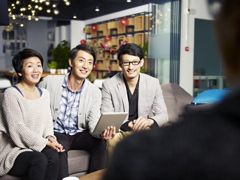 Hombres de negocios jovenes que hablan con el jefe foto de archivo