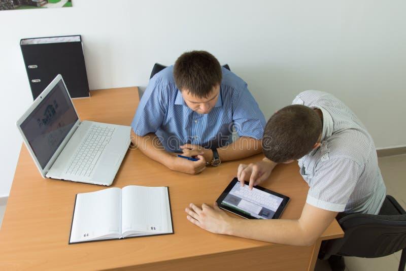 Hombres de negocios jovenes que hojean en la tableta imagen de archivo