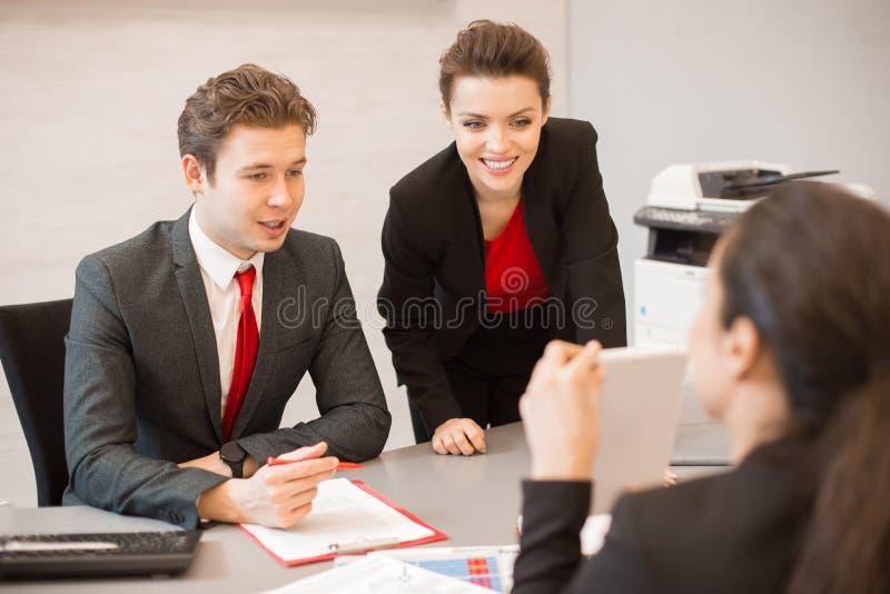 Hombres de negocios jovenes que llevan la reunión imagen de archivo