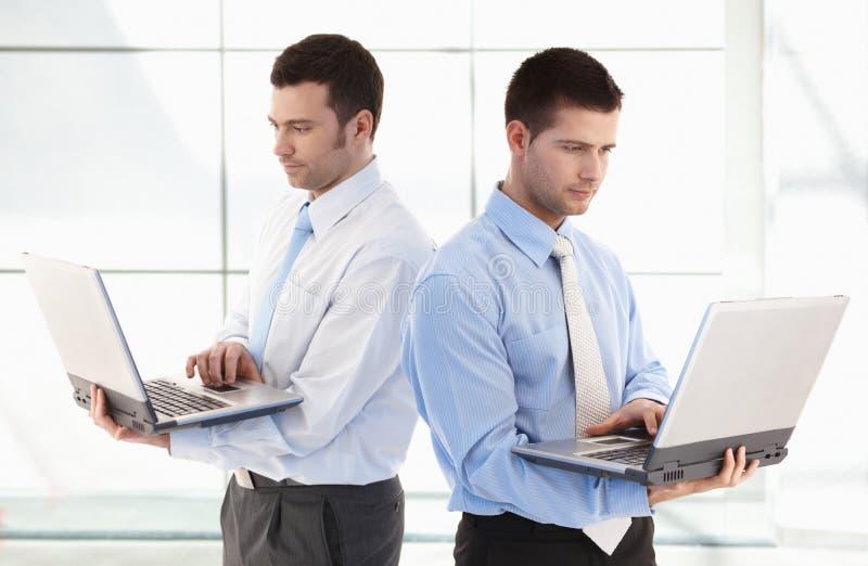 Hombres de negocios jovenes que se colocan con la computadora portátil en manos imagenes de archivo