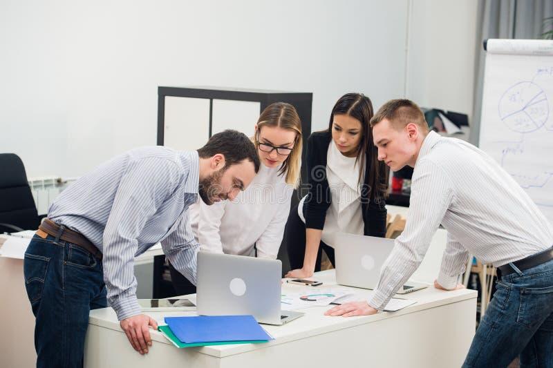 Hombres de negocios jovenes que se sientan en oficina durante la reunión y que discuten con papeleo usando los ordenadores portát foto de archivo libre de regalías