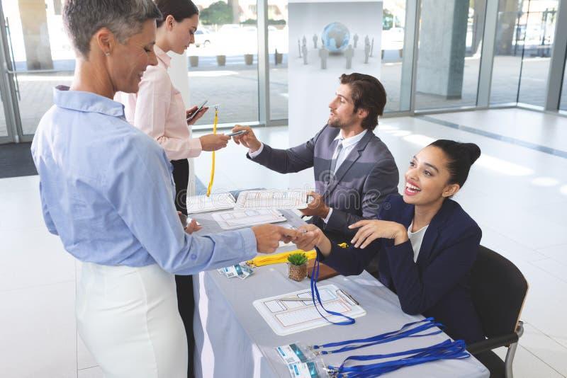 Hombres de negocios de la incorporación en la tabla del registro de la conferencia fotografía de archivo libre de regalías