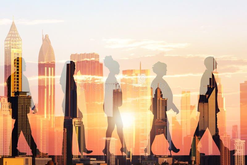 Hombres de negocios de la silueta y edificios modernos durante puesta del sol foto de archivo libre de regalías
