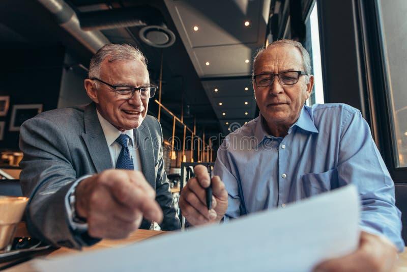 Hombres de negocios mayores que discuten en el informe financiero foto de archivo