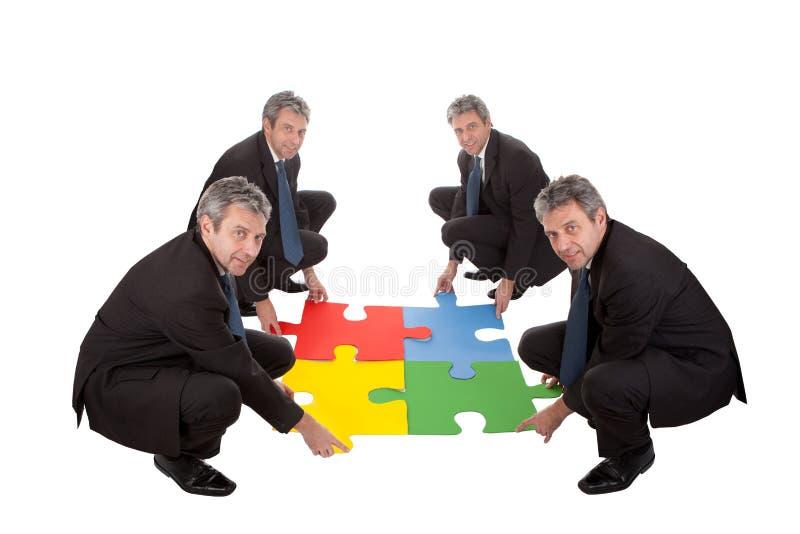 Hombres de negocios mayores que ensamblan un rompecabezas de rompecabezas fotografía de archivo