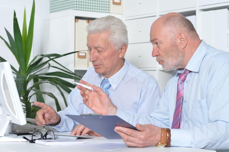 Hombres de negocios mayores que trabajan junto foto de archivo