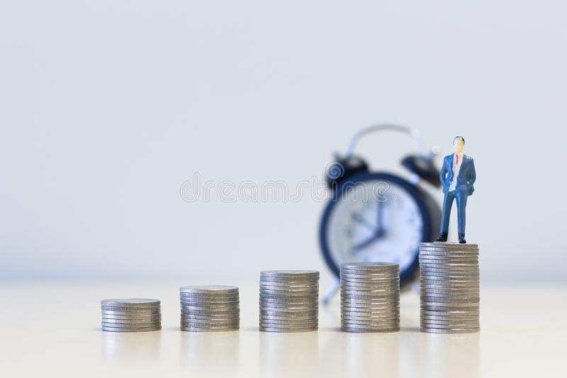 Hombres de negocios miniatura de la gente que se colocan en pila de las monedas del dinero Dinero y conceptos financieros finanza fotos de archivo