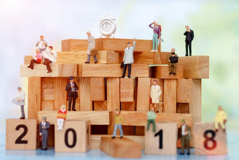 Hombres de negocios miniatura que se sientan en el bloque de madera con el número 2018, fotos de archivo libres de regalías