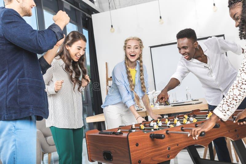 hombres de negocios multiculturales que celebran triunfo mientras que juega la tabla fotos de archivo