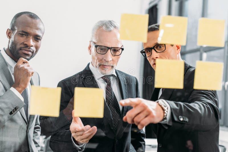 hombres de negocios multiculturales que miran notas durante la reunión imagen de archivo libre de regalías