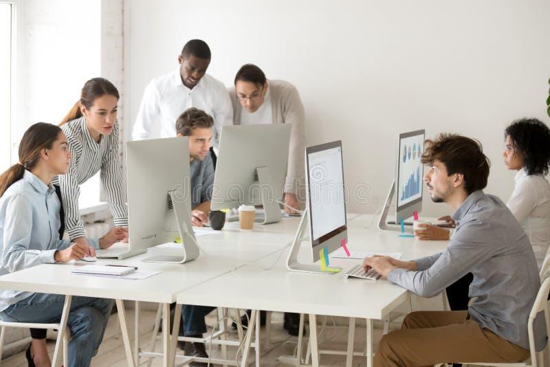 Hombres de negocios multirraciales enfocados que trabajan en línea en los ordenadores foto de archivo libre de regalías