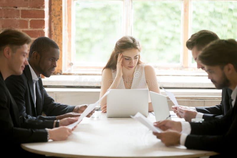 Hombres de negocios multirraciales serios que llevan a cabo el documento de la lectura en la reunión imagenes de archivo
