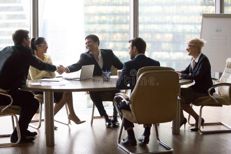 Hombres de negocios multirraciales sonrientes que se sientan en la reunión imagen de archivo