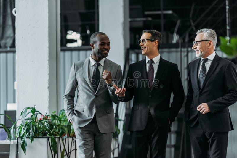 hombres de negocios multirraciales sonrientes que tienen conversación mientras que camina foto de archivo