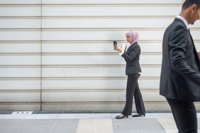Hombres de negocios musulmanes en su Smartphone mientras que en un descanso para tomar café, caminando hacia uno a Profundidad de imagen de archivo
