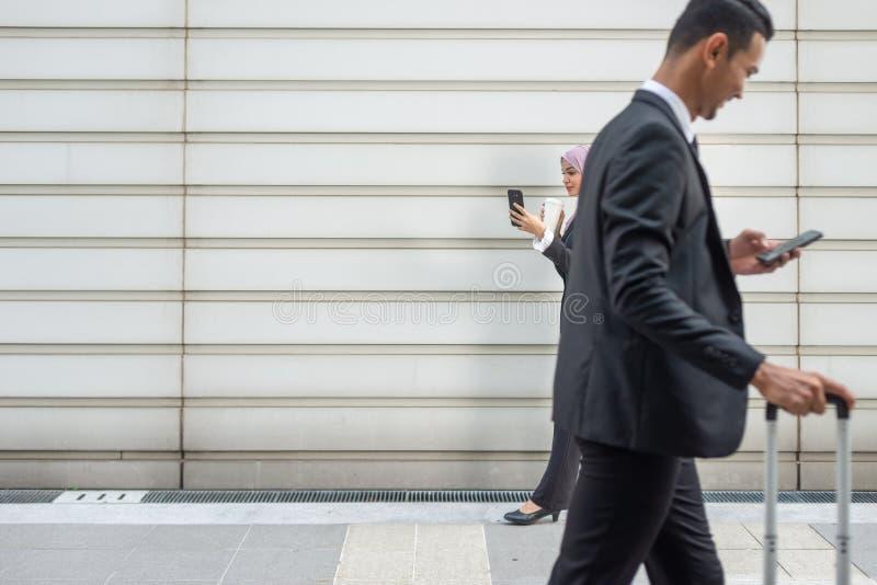 Hombres de negocios musulmanes en su Smartphone mientras que en un descanso para tomar café, caminando hacia uno a Profundidad de imágenes de archivo libres de regalías
