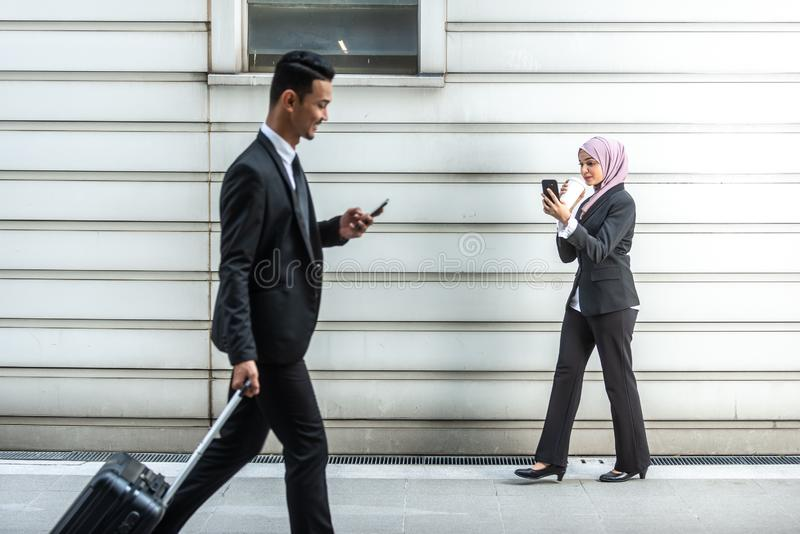 Hombres de negocios musulmanes en su Smartphone mientras que en un descanso para tomar café, caminando hacia uno a Profundidad de fotografía de archivo libre de regalías