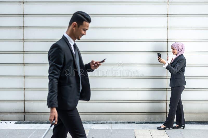 Hombres de negocios musulmanes en su Smartphone mientras que en un descanso para tomar café, caminando hacia uno a Profundidad de fotos de archivo
