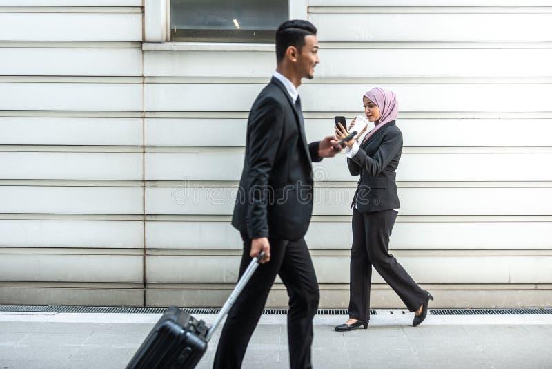 Hombres de negocios musulmanes en su Smartphone mientras que en un descanso para tomar café, caminando hacia uno a Profundidad de foto de archivo libre de regalías