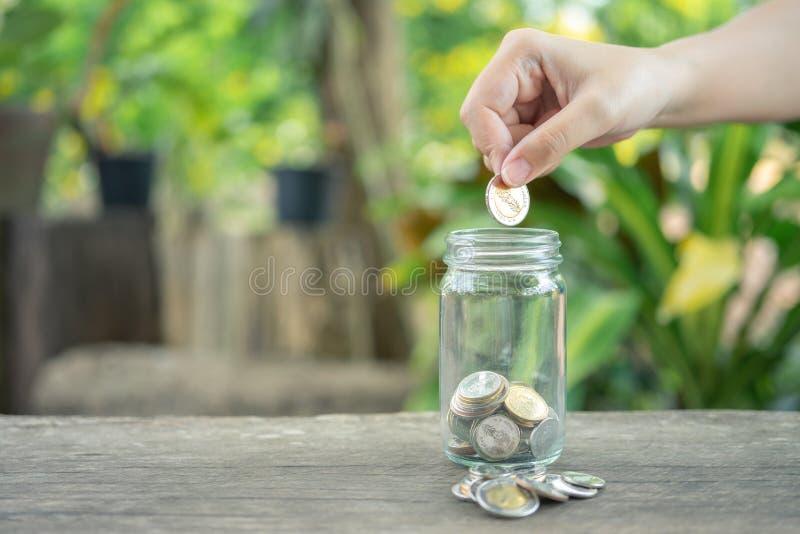 Hombres de negocios Pon la moneda en un frasco de vidrio Para ahorrar dinero, ahorrar dinero en inversiones, gastar dinero cuando  fotos de archivo