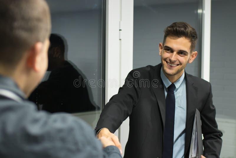Hombres de negocios que agitan con sus manos fotos de archivo