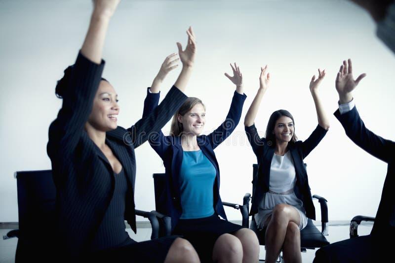 Hombres de negocios que animan con los brazos en el aire imagen de archivo libre de regalías